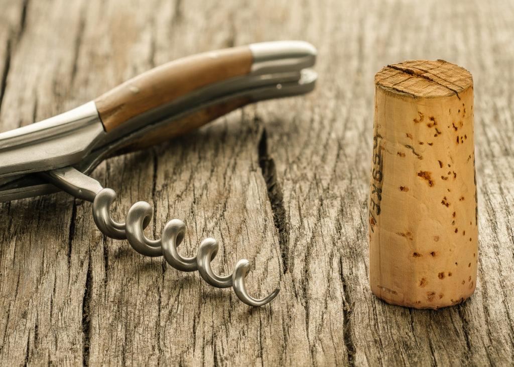 Korkenzieher mit Korken auf rustikalen Holz