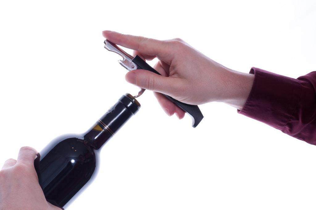Korkenzieher und Flasche in Hand