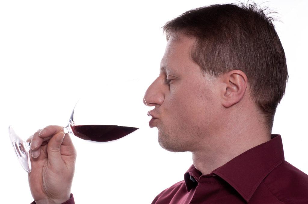 Mann geniesst ein Glas Rotwein